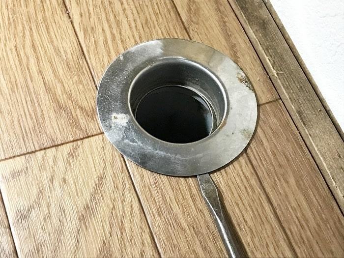 排水ホースを抜き取り排水口に取り付けられているカバーをマイナスドライバーでこじ開ける